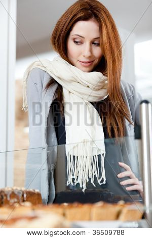 Woman in scarf looking at the bakery window full of different pieces of pies