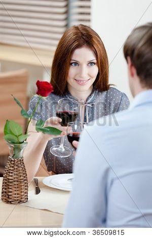 Casal é no restaurante sentado à mesa com vaso e carmesim subiu nele