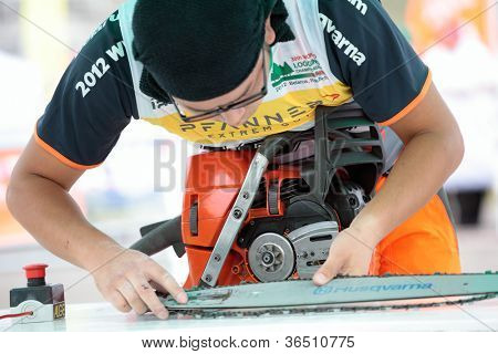 RAUBICHI, BELARUS - AUGUST 25: Japanese Hiroki Shirakawa fits another chain during World Logging Championship in Raubichi, Minsk region, Belarus at August 25, 2012
