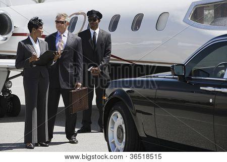 Mensen uit het bedrijfsleven verslagen bespreken met chauffeur in de achtergrond op het vliegveld