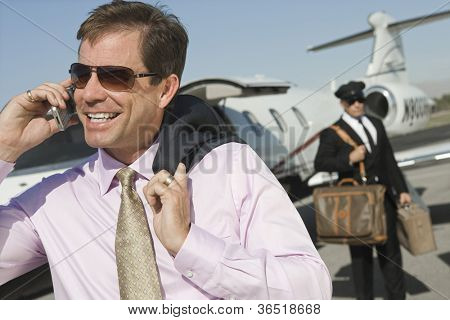 Middle aged businessman using cell phone with driver holding luggage in the background at airfield