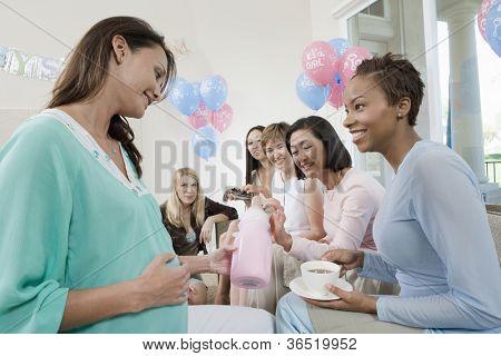 Schwangere Frau mit Freunden halten Babyflasche auf ein Baby-Dusche