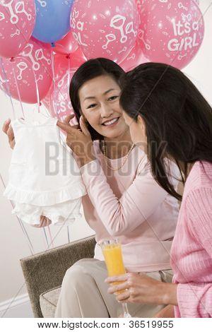 Middle aged Woman zeigen Babykleidung Freund auf ein Baby-Dusche
