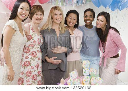 Porträt einer schwangeren Frau mit Freundinnen auf einer Baby-Dusche