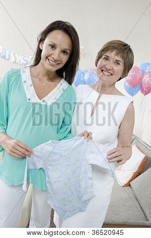 Porträt von glücklich schwangere Frau mit Mutter, die Abhaltung von Babykleidung auf ein Baby-Dusche