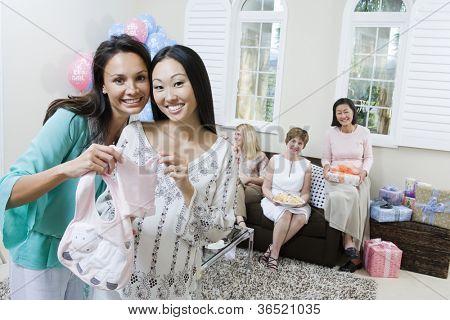 Fröhlich schwangere Frau und Freund, die Abhaltung von Babykleidung auf ein Baby-Dusche