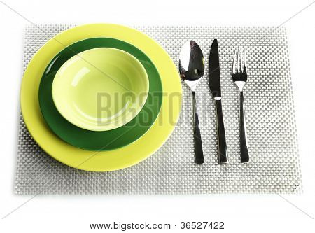Green empty plates with fork, spoon and knife on a grey tablecloth