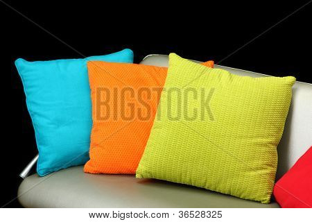 Colorful pillows on couch on black background
