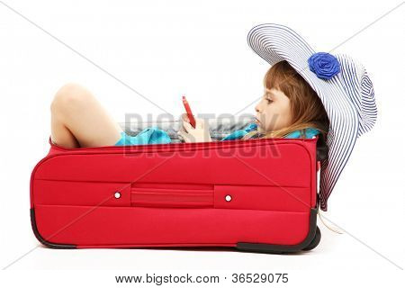 Portrait of little girl in travel case with hat isolated on white