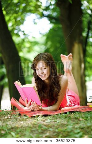 Woman reading book in park during spring or summer time.