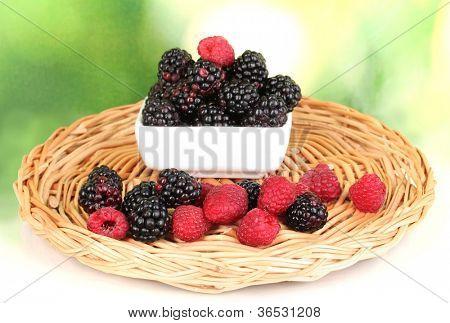 Ripe raspberries and brambles on nature background