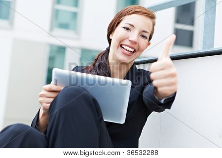 Happy woman with a tablet pc holding her thumbs up