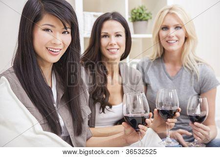 Interracial Freundesgruppe drei schöne junge Frauen trinken zu Hause Rotwein zusammen