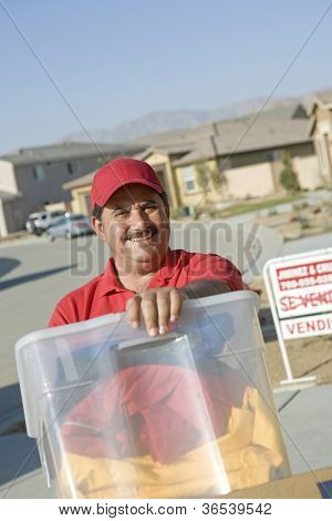 Portrait of a middle aged deliveryman carrying container into new house
