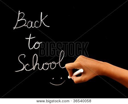 "Handwriting phrase ""back to school"" on blackboard in classroom, conceptual image of school time, teacher arm holding chalk and writing word, education and knowledge concept"