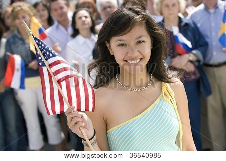 Portrait of young woman holding American flag with people in the background
