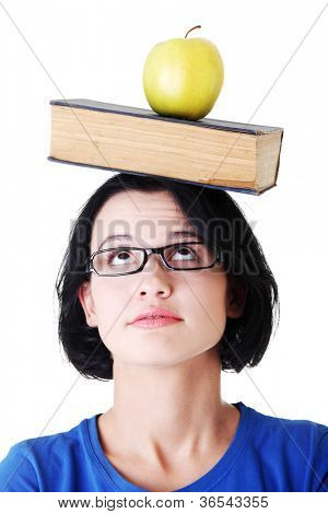 Student with an apple and book on her head , isolated on white