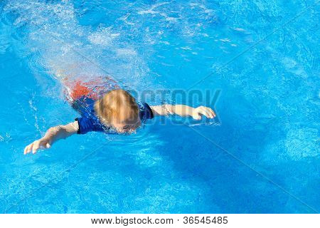 Young boy learning to swim with his clothes on in a pool