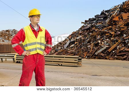 Worker, with overalls, a hard hat and safety goggles standing at the entrance of a metal scrap yard