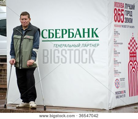 MOSCOW - SEPTEMBER 2: Disabled man near poster with logo