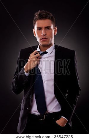 A Young businessman loosing his tie. on black background