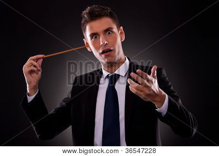 Young conductor sticking his baton in his ear. Young businessman sticking a conductor's baton in his ear.