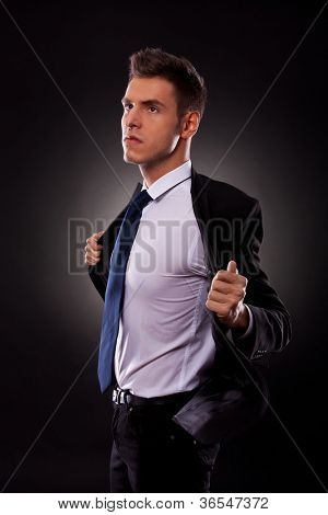 45 degree angle view of a young businessman taking off his jacket angrily, looking away from camera