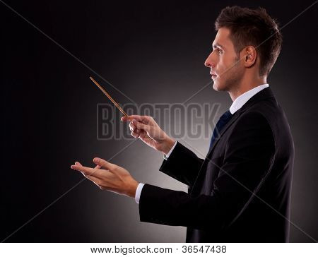 Side view of a young business man directing with a conductor's baton