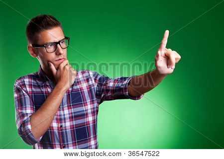 Young casual man pensively selecting something on an imaginary screen. Over green background