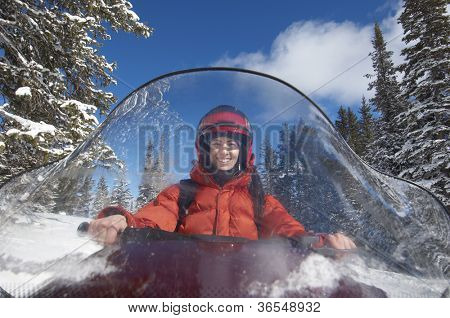 Front view of a woman riding snowmobile on a sunny day