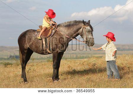dos niños felices caballo sobre fondo natural