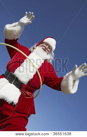 Santa Claus doing hula hoop against clear sky