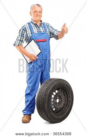 Full length portrait of a mature mechanic with tyre isolated on white background