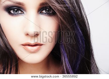 Portrait of beautiful young woman with long colored brown hair and bright make-up