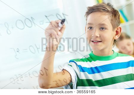 Portrait of handsome learner doing sums with schoolmate on background