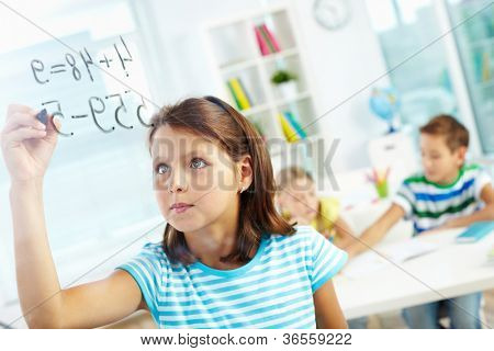 Portrait of lovely girl doing sums on transparent board with schoolmates on background