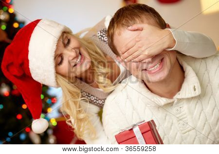 Portrait of happy woman closing male�¢??s eyes by her hands while holding giftbox in front of him