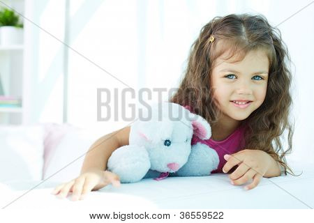 Portrait of lovely girl with teddybear looking at camera