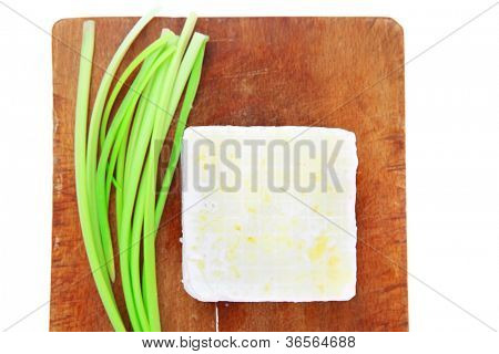 dairy food : feta white cheese cubes over small cut wooden plate isolated over white background