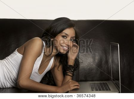Young woman using laptop computer on sofa.