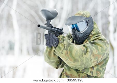 paintball extreme sport player wearing protective mask and comouflage clothing with marker gun at winter outdoors