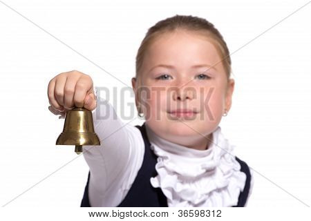 Winking Young school girl ringing a golden bell on white backgro