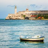 The Castle of El Morro, a worldwide known  landmark of Havana with a small fishing boat on the foreground poster