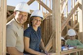 Portrait of happy family wearing hardhats at their incomplete house