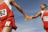stock photo of relay  - Male athletes passing baton in relay race - JPG