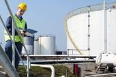 stock photo of silos  - Engineer with a clipboard taking notes of the quality and state of oil silos of a petrochemical industry for safety reasons - JPG