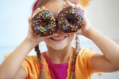 stock photo of donut  - Cute kid girl eating sweet donuts - JPG