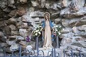 stock photo of atonement  - The statue of the Virgin Mary in a stone cave - JPG