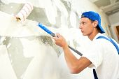 stock photo of interior decorator  - One painter with paint roller making wall prime coating  at home repair renovation work - JPG