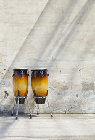 foto of congas  - two congas in front of a vintage wall - JPG